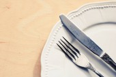 Fork and table knife on empty white plate. Restaurant concept.