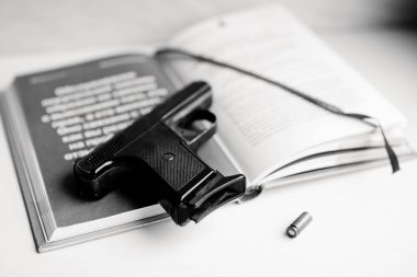 Detective novel concept with gun, book and bullet. Black and white photo.