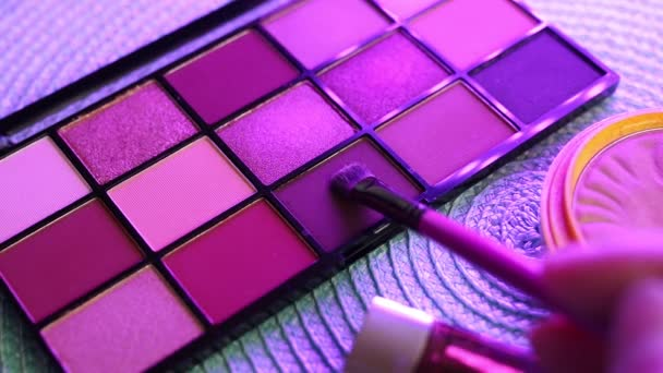 A palette with eye shadows and a makeup brush in slow motion. Close up of woman make up cosmetics palette with differents powder colors.