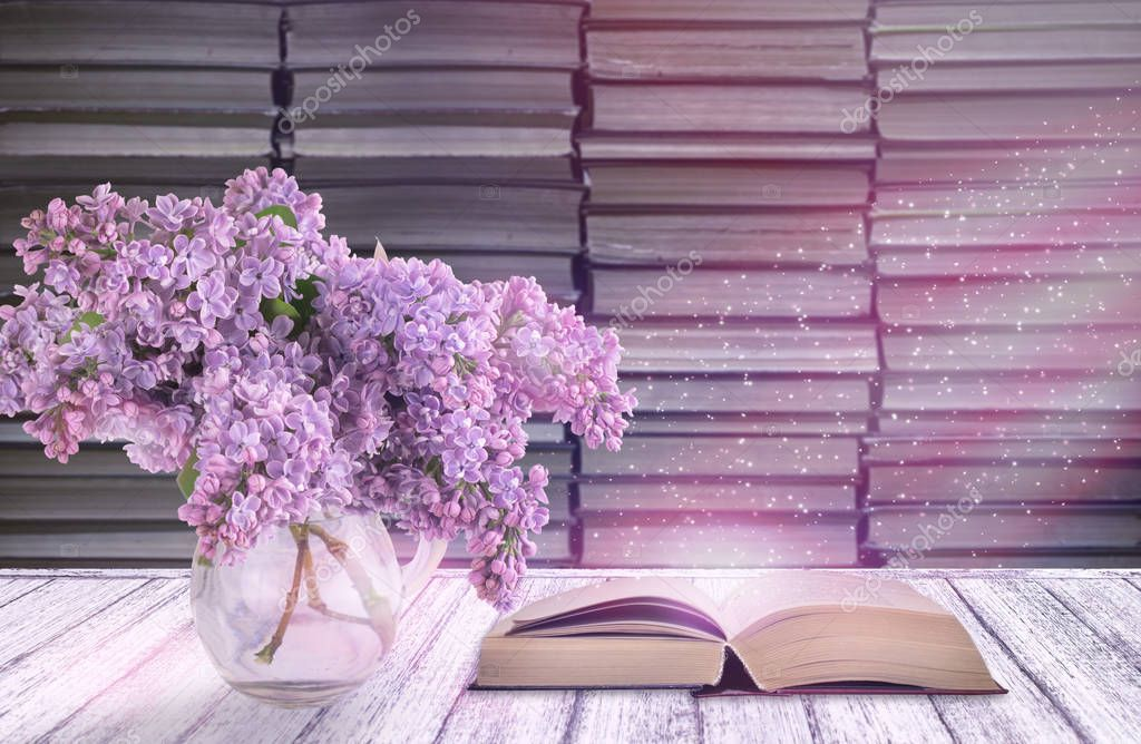 Room interior with lilac flowers in glass vase and open fairytale book on table in shabby chic style on background of stack of old books