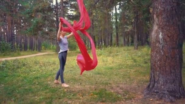 Mladá žena cvičí vzdušné jóga cvičení nebo antigravitační jóga venku. Létání, fitness, roztáhnout, rovnováhu, zdravého životního stylu lidí. Žena používající houpací síť.