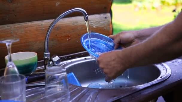 Muž mytí nádobí v kovové jímky venku