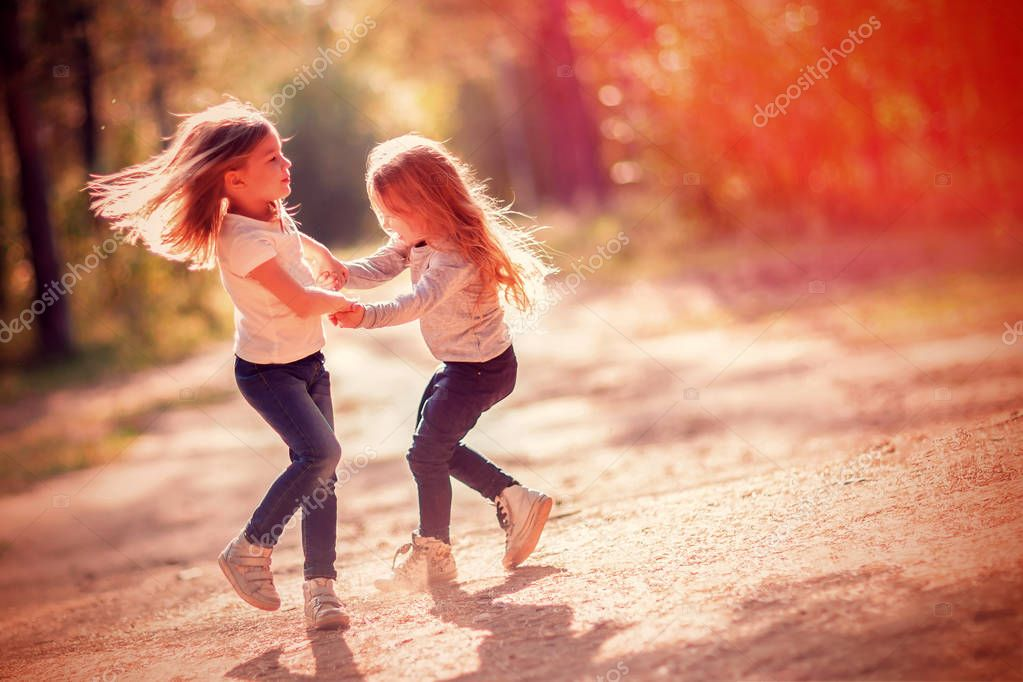 Two little girls dancing and having fun together outdoors