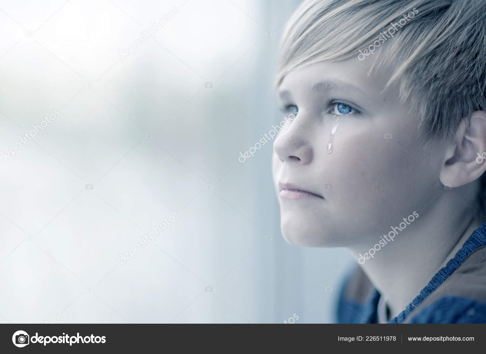 Crying boy looks out the window portrait of sad blond teen 12 14 year old stock image