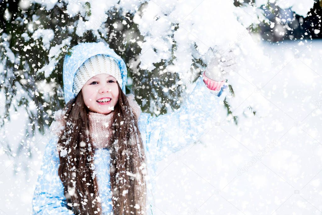 A kid is looking so happy shaking hands with a snowy fir-tree! A girl's long hair became snowed while walking.