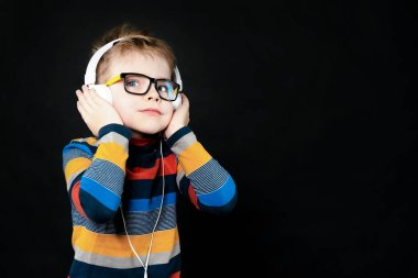 A boy in headphones listens to music. On a black background in t