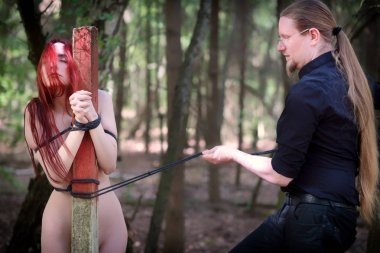 Young beautiful sexy proud red-haired woman is lovingly handcuffed to a post by her master