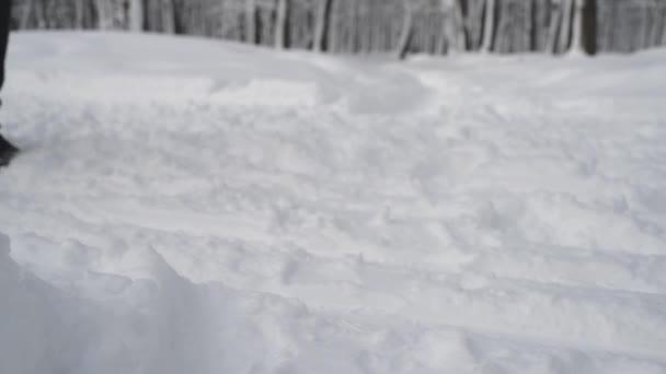 Nohy běží žena na zasněžený zimní les. Detailní záběr.