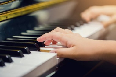 Selective focus to fingers of woman teaching boy to play the piano. Hands from two people playing piano with music notation. There are musical instrument for learning music.