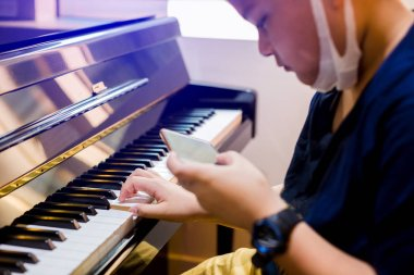 Selective focus of kid play the piano with smart phone for learning music. There are musical instrument for learning music.
