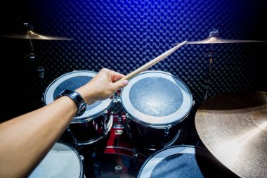 man playing the drum set with wooden drumsticks in music room , the concept of musical instrument
