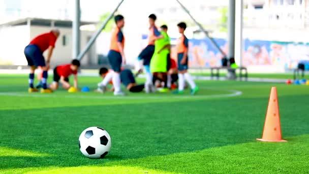 Fotbalový míč a kužele značky na zelený umělý trávník s rozmazaný z přípravy fotbalista. Fotbalové akademie