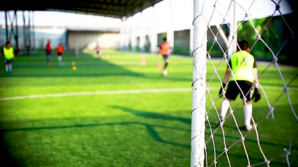 White goalposts and mesh of goal with blurry of soccer goalkeeper and soccer players are training to shoot ball. football academy.