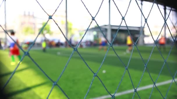 Mesh in football field with blurry soccer players playing and training soccer game. Soccer or football training in academy.
