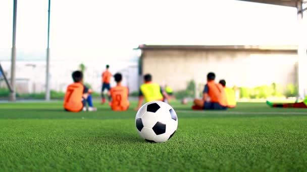 fotbal mezi markerovými kužely na zeleném umělém trávníku s rozmazaným fotbalovým týmem, rozmazaný dětský fotbalový hráč joggingu mezi značkovací kužele a řídicí koulí s fotbalovým vybavením na fotbalové akademii.