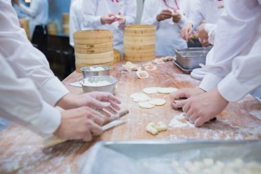 Dim Sum chefs working wrapping dumplings at famous restaurant in
