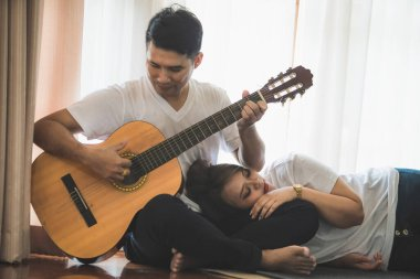Young Asian couple wearing a white T-shirt is playing the guitar and singing together in a warm home.