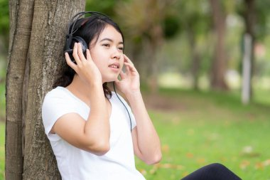 Young woman is listening to music with headphones in the park.