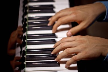two male hands on the piano. palms lie on the keys and play the keyboard instrument in the music school. student learns to play. hands pianist. black dark background. top view