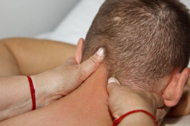 professional medical massage of the head and neck. woman doctor massages a man athlete in a massage room. body and health care. procedure for recovery from pain after sports workouts