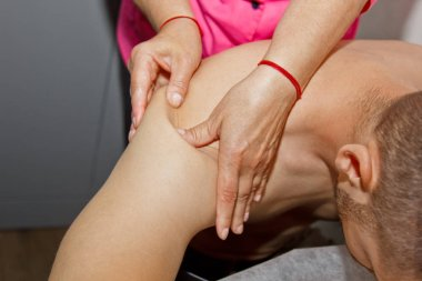 professional therapeutic shoulder and neck massage. woman doctor massages a man athlete in a massage room. body and health care. procedure for recovery from pain after sports workouts