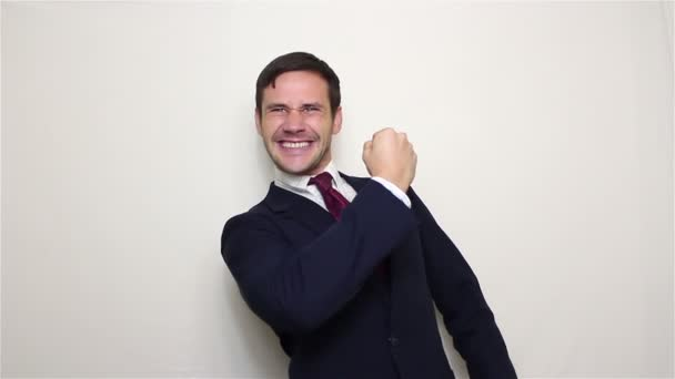 Handsome young businessman actively expresses joy, makes a gesture with his hand and says yes.