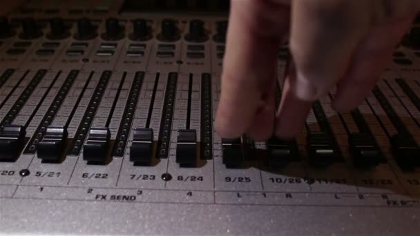 Sound engineer raises the sliders of the sound tracks on the sound mixer.