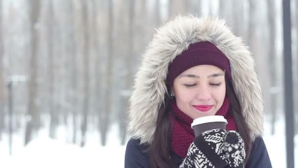 Krásná mladá dívka si zimní pohled a pití kávy v zasněženém parku.