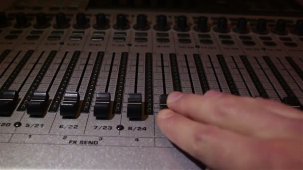 Sound engineer lowers the sliders of the sound tracks on the sound mixer, turning off the sound.