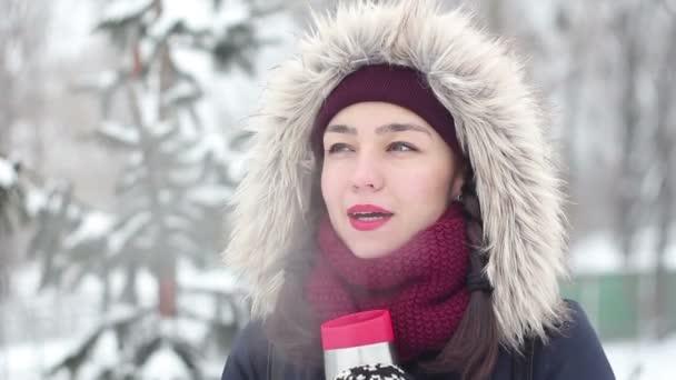 Krásná mladá dívka pije kávu z termosky v destinaci winter park.