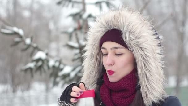 Krásná mladá dívka má pití kávy z termosky na procházce v parku zimní.