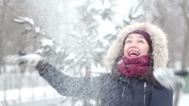 Beautiful young girl throws up snow with her hands and actively expressed joy, laughs and claps her hands.