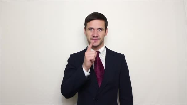 Young handsome businessman is showing a menacing hand gesture slitting his throat.