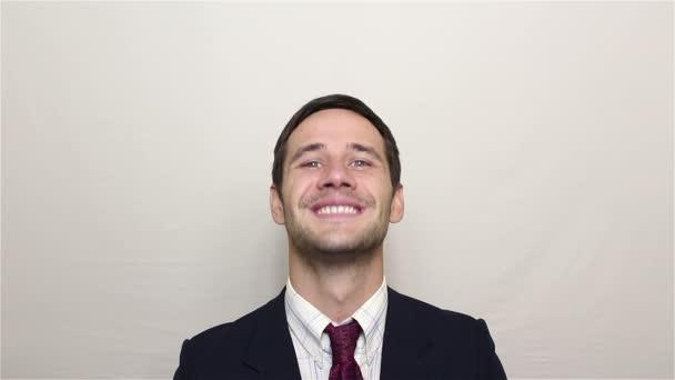 junger gutaussehender Geschäftsmann lächelt breit und nickt zustimmend.