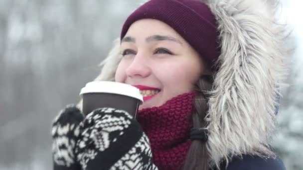Beautiful young girl drinks coffee in the winter forest.