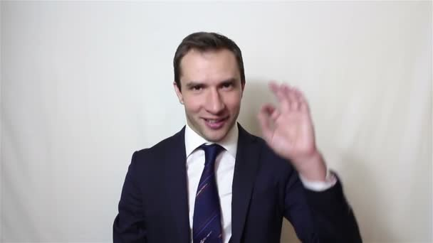 Young handsome businessman says ok and shows gesture ok