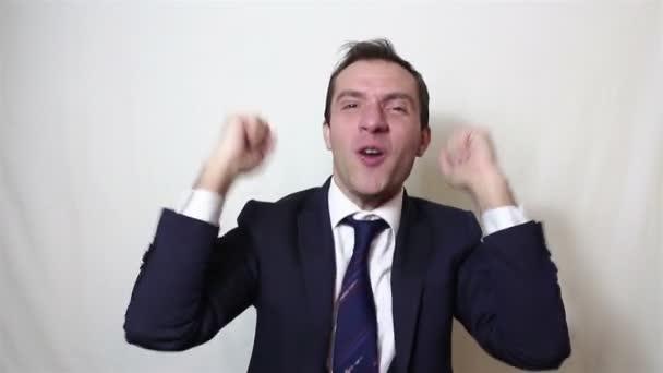Pohledný mladý podnikatel aktivně vyjadřuje radost tleskání a hlasitý smích
