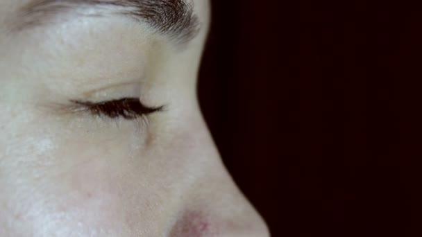 Mladá krásná dívka otevře své zelené hnědé oči a dívá se do dálky.