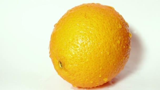 Drops of water flow down a juicy ripe orange.