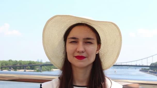Zavřít portrét krásná mladá dívka v bílém klobouku hledí do kamery a usmívá se. Mladá přitažlivá dívka v bílém klobouku zvedá zrak k obloze a pobledá z slunečních paprsků.