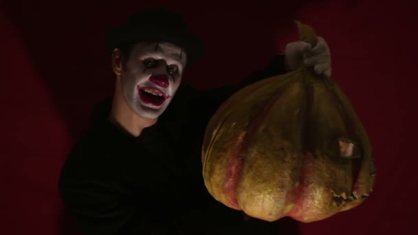 Scary clown holds a pumpkin mask in his hands. A scary man in a clown makeup holds a pumpkin for Halloween. A scary clown holds a Jack-O-Lantern in his hands with luminous eyes and a mouth.