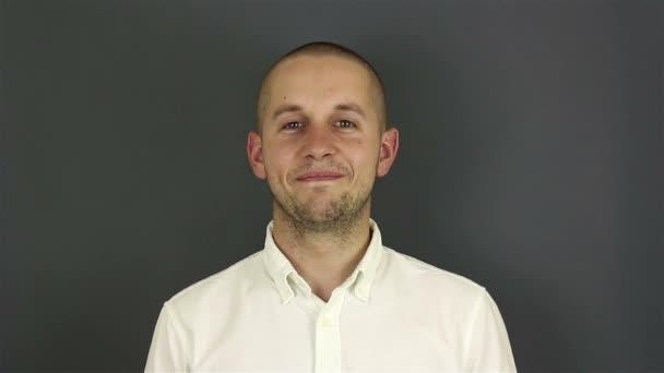 Zblízka portrét mladého atraktivního chlapa, dívá se do kamery a usmívá se. Portrét na šedém pozadí.