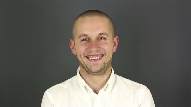 Zblízka portrét mladého atraktivního chlapa, se zasměje a podívá se do kamery.
