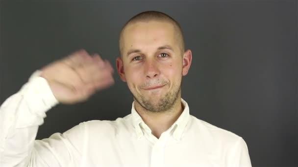 Nahaufnahme Porträt eines jungen attraktiven Typen, er lächelt und winkt zur Begrüßung seinen Freunden zu.