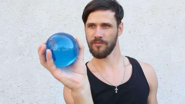 Mladý atraktivní chlap je zapojen do kontaktního žonglování. Muž žongluje s modrou průhlednou koulí.