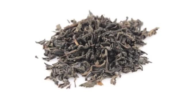 Közelkép egy rotáció nagy levél fekete tea fehér háttérrel. A szárított fekete tealevelek egy tányéron forognak. Egy maroknyi nagy levél fekete tea forog egy fehér tányéron..