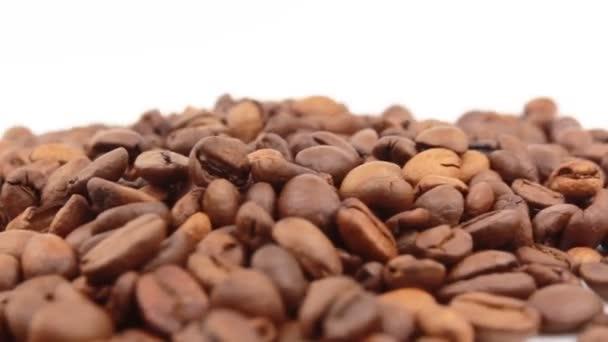 Nahaufnahme der Rotation von Kaffeebohnen. Geröstete aromatische Kaffeekörner rotieren auf einem Teller.