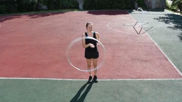 Eine attraktive Frau, eine Zirkusartistin, dreht Hula-Hoop-Reifen auf der Straße und verbessert ihre Fähigkeiten. Straßenkünstler übt Hula-Hoop-Spinning.