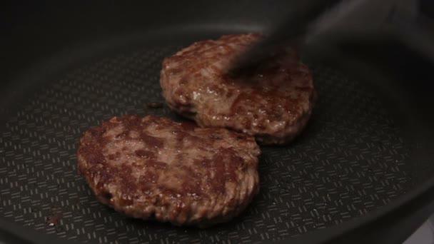 Šéfkuchař dává hovězí placky na gril. Šťavnaté hovězí řízečky, smažené na pánvi. Detailní záběr hovězí kotlety na hamburger na grilu. Šéfkuchař převrátí grilovanou kotletu.