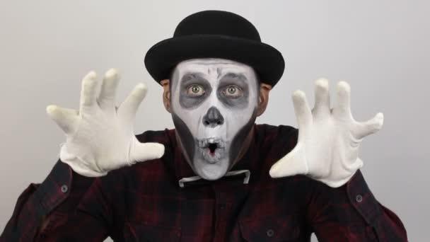 Hrozný muž v klaunských maskérských grimasách a dělá děsivá gesta. Děsivý klaun se podívá do kamery a hrozně se zasměje. Děsivé grimasy klauna, který se dívá do kamery. Halloween kostým.